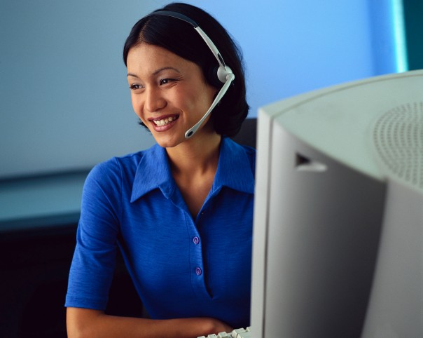 Businesswoman Wearing Phone Headset by a Computer